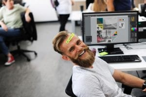 Blond bearded man smiles and leans back in his office chair with a sticky note on his face that reads 'be happy' with graphics on his computer screen
