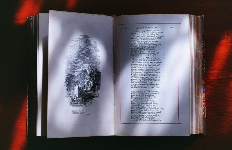 Antique poetry book open to 'The Lady of the Lake' with a black & white image on the other page, resting on a red background