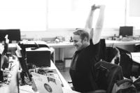 Happy man wearing black t-shirt stretches over his head at his desk in front of a computer in black and white