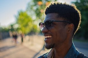 Side-view portrait of a black man smiling wearing sunglasses and green trees blurry in the background