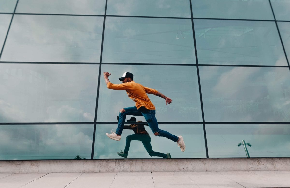 A young man in an orange shirt and denim jeans with ripped knees, white shoes and a hat, jumps into a running man position in front of a reflective glass wall