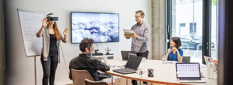 A meeting taking place while a young woman wears a virtual reality headset in from of an SEO flipboard while a man with a tablet looks on beside a tv screen showing clouds and others use their laptops