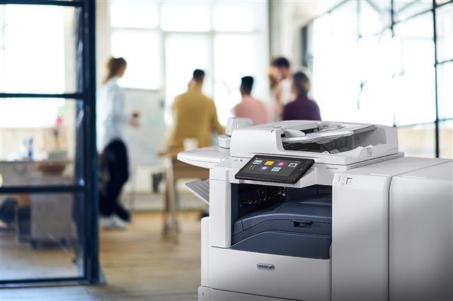 Xerox printer with touch screen and people in the background of a