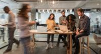 Desktop Xerox printer on wooden table with people looking at laptop, blurry woman in foreground, glass office