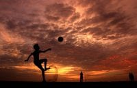 A silhouetted boy kicks a soccer ball in the foreground of a yellow, red, orange, and pink sunset and kicks up dirt