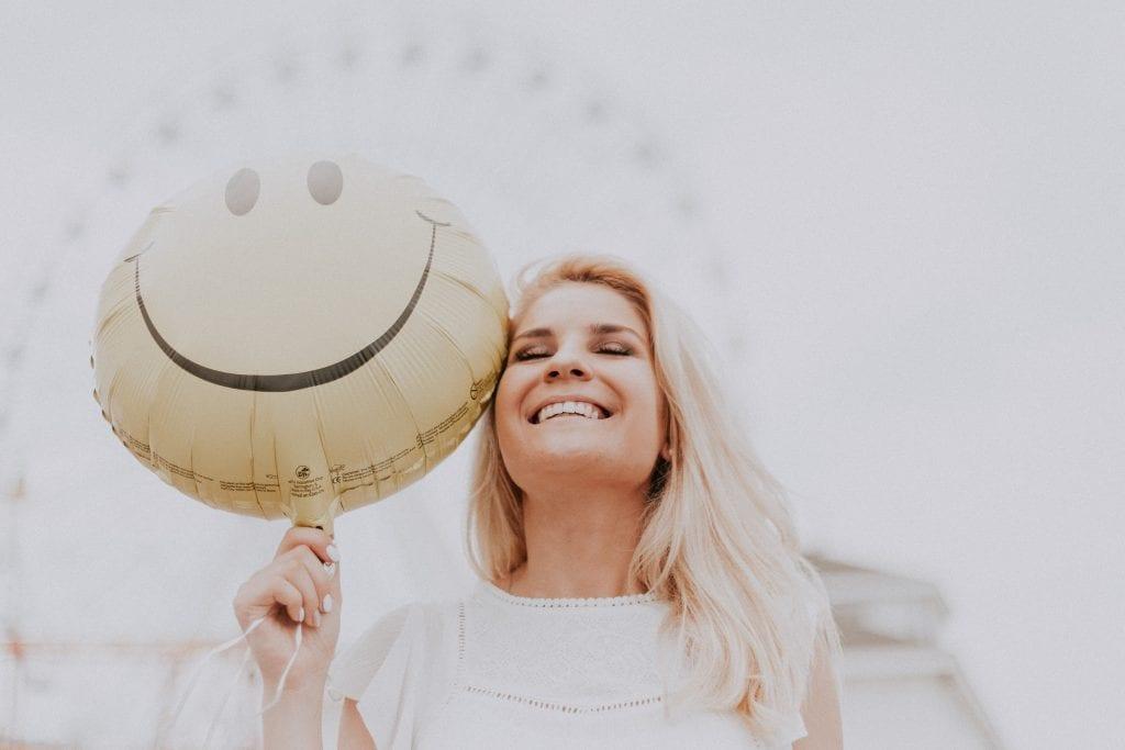 Beautiful blonde woman wearing white smiling, holding yellow smiley-face balloon
