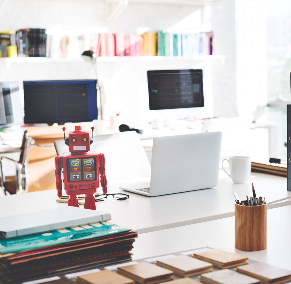 Red toy robot with yellow eyes on work desk with laptop, computer screens, books, pens, and papers