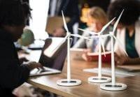 Three desktop solar powered model wind turbines demonstrating renewable energy while three women work on laptops in background