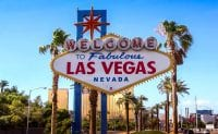 """Iconic """"Welcome to Fabulous Las Vegas Nevada"""" sign in daylight with blue sky and palm trees on strip"""