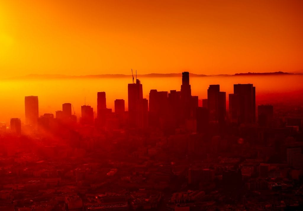 City at sunset with sun shining through orange, yellow, and red low clouds, mountains in background