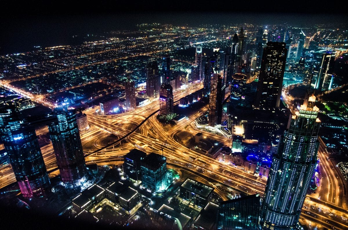 A busy highway intersection in a city at night with lit up buildings of blue and purple