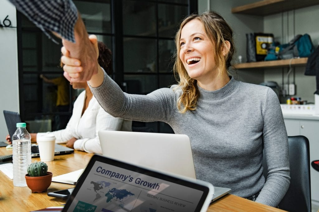 Smiling woman wearing sweater shakes man's hand in front of a laptop of company growth