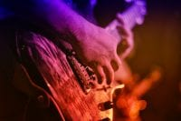 Hands close up playing an electric guitar under blue, purple, red, and orange stage lights