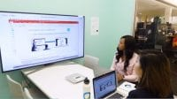 Two women sit at a desk in front of a Cisco webex monitor and laptop watching a business presentation